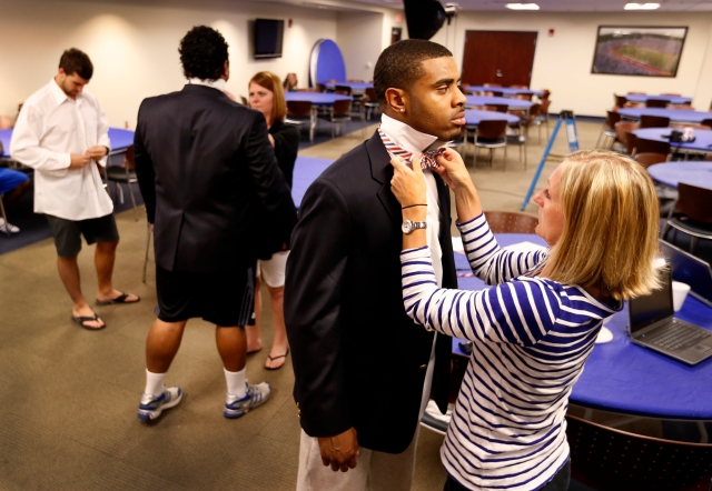 Erin Penning and Katy Lonergan tying bow ties for the KU football team.