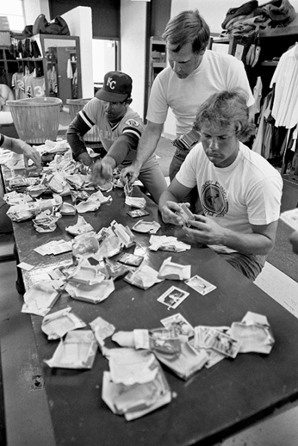 Brett digging through packages of bubble gum cards to collect their favorites with Marty Pattin and Cookie Rojas.