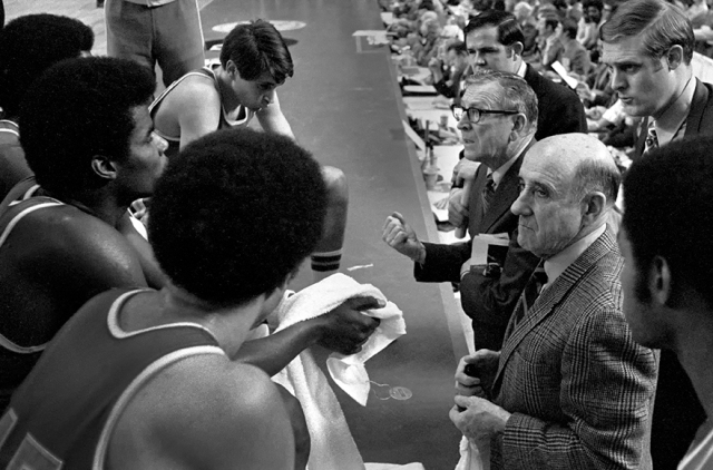 Legendary coach John Wooden urging on his team during a timeout.