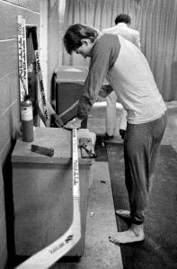 Gretzky cutting down a hockey stick before the game.